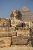 The Egyptian sphinx. The great egyptian Sphinx of Giza with ancient pyramids on the background Stock Photos