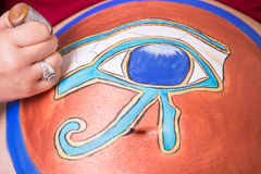 Egyptian symbol in pregnant belly. Makeup artist creating Eye of Horus painting on the belly of a pregnant woman royalty free stock images