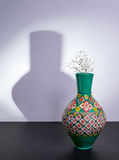 Egyptian traditional pottery vase and small flowers with harsh shadow Stock Photos