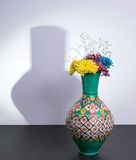 Egyptian traditional pottery vase and three flowers with harsh shadow Stock Image