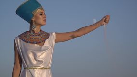 Egyptian wife of Pharaoh lets out a handful of sand posing in the desert at sunset