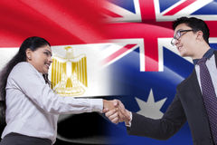 Egyptian woman shaking hands with Australian person Stock Photo