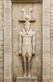 Egyptisch standbeeld van een mensencijfer aangaande de muurvoorgevel stock foto