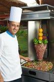 Arabische chef-kok die kebab maakt stock afbeelding