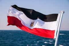 Egyptisk flagga som svävar i solen med Röda havet i bakgrunden arkivfoto