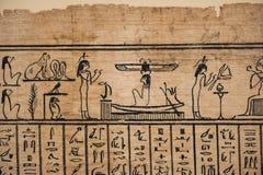 Egyptiska hieroglyf tecken på papyruset arkivbilder