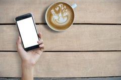 Egzamin próbny ręki chwyta up telefonu komórkowego latte i ekranu pusta sztuka dalej zaleca się fotografia royalty free