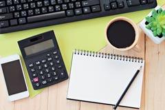 Egzamin próbny up biuro stołu biurka workspace z pustym notatnikiem, mądrze telefonem, kalkulatorem, komputerową klawiaturą i kaw Obrazy Royalty Free