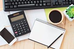 Egzamin próbny up biuro stołu biurka workspace z pustym notatnikiem, mądrze telefonem, kalkulatorem, komputerową klawiaturą i kaw Zdjęcie Stock