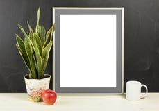 Egzamin próbny up pusta fotografii rama z garnkiem, kubkiem i jabłkiem na wo rośliny, Obrazy Stock