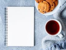 Egzamin próbny z w górę pustego Notepad prześcieradła, herbaty, ciastek i dziający ciepłego, zdjęcia stock