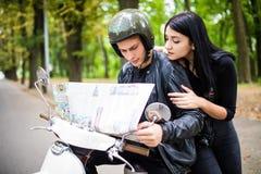 Egzamininujący mapę wpólnie Piękny młody kochający pary obsiadanie na hulajnoga wpólnie i egzamininujący mapę Fotografia Royalty Free