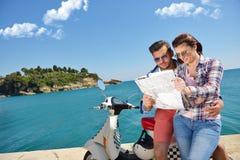 Egzamininujący mapę wpólnie Piękny młody kochający pary obsiadanie na hulajnoga wpólnie i egzamininujący mapę Zdjęcie Stock