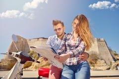 Egzamininujący mapę wpólnie Piękny młody kochający pary obsiadanie na hulajnoga wpólnie i egzamininujący mapę Zdjęcia Stock
