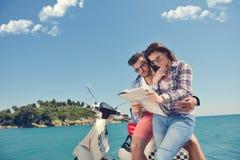 Egzamininujący mapę wpólnie Piękny młody kochający pary obsiadanie na hulajnoga wpólnie i egzamininujący mapę Obraz Stock