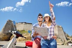 Egzamininujący mapę wpólnie Piękny młody kochający pary obsiadanie na hulajnoga wpólnie i egzamininujący mapę Obrazy Stock