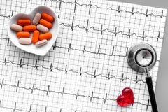 Egzamininuje serce zapobiegać kierową chorobę Serce znak, kardiogram, pigułki, stetoskop na popielatego tła odgórnym widoku Obrazy Stock