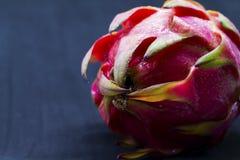 Egzotyczny owocowy Dragonfruit z menchii i zieleni skórą na czarnym tle Fotografia Stock