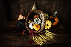 EH2_2065. A cornucopia or horn of plenty spilling vegetables out on to a worn wooden harvest table. Dark and moody low key presentation royalty free stock photography