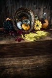 EH2_2074. A cornucopia or horn of plenty spilling vegetables out on to a worn wooden harvest table. Dark and moody low key presentation. Room for copy space royalty free stock photography