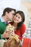 Ehemann-überraschende Frau mit Weihnachtsgeschenk Lizenzfreie Stockfotos