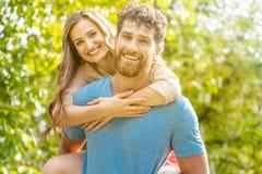 Ehemann bringt seine Frau auf seinem zurück lizenzfreies stockfoto