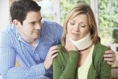 Ehemann, der die Frau leidet mit Nackenverletzung tröstet Lizenzfreies Stockfoto