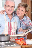 Ehemann, der ein Kochbuch betrachtet Stockfoto