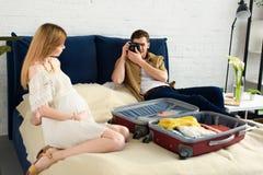 Ehemann, der Foto des schwangeren Frauvorbereitens macht lizenzfreie stockbilder