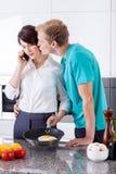 Ehemann, der seine Frau während der Frühstücksvorbereitung küsst Stockbild