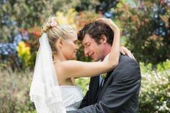 Ehemann, der seine neue blonde Frau umarmt Stockbild