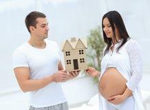 Ehemann, der seiner schwangeren Frau einen Plan ihres zukünftigen Hauses zeigt Lizenzfreie Stockbilder