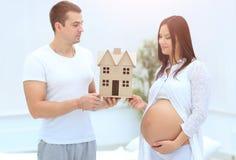 Ehemann, der seiner schwangeren Frau einen Plan ihres zukünftigen Hauses zeigt Lizenzfreie Stockfotos
