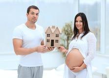 Ehemann, der seiner schwangeren Frau einen Plan ihres zukünftigen Hauses zeigt Lizenzfreie Stockfotografie