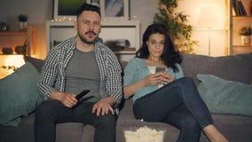 Ehemann, der während Frau verwendet den Smartphone zu Hause bespricht Nachrichten fernsieht stock footage