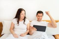 Ehemann gewinnt das Wetten und Frau wird ärgerlich stockfoto