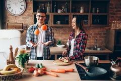 Ehemann jongliert Orangen während Fraukochen stockbilder