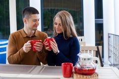 Ehemann mit Frau auf heißem Kaffee und Tee des Feiertagsgetränks stockbilder