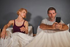 Ehemann oder Freund, der Handy im Bett und misstrauisches frustriertes Frau- verwenden oder Freundingefühlsumkippen, das Verrat v stockfotografie