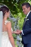 Ehemann setzt einen Ehering auf den Finger der Braut auf ihrem Heiratsd Lizenzfreies Stockbild