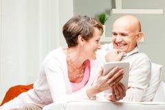 Ehemann und Frau, die über einem Tabletten-PC kichern Lizenzfreies Stockbild