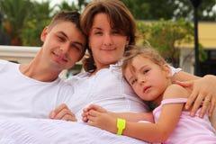 Ehemann und Frau und Tochtersitzen und -umarmung Lizenzfreies Stockfoto