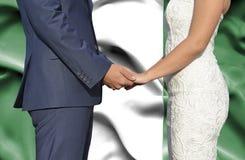 Ehemann- und Frauhändchenhalten - Begriffsphotographie der Heirat in Nigeria stockbild