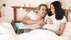 Ehemann und schwangere Frau, die online im Bett kaufen lizenzfreie stockbilder