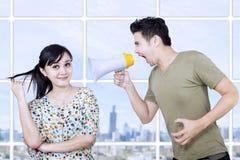 Ehemann verärgert an der Frau, die Megaphon verwendet Stockbild