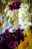 Eheringe auf Blumen Stockfotografie