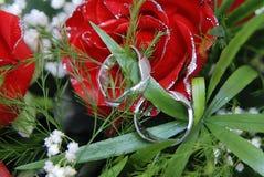 Eheringe auf Blumenstrauß der roten Rosen Lizenzfreie Stockbilder