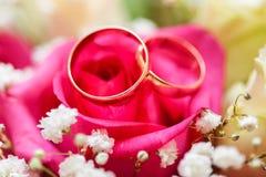 Eheringe auf Brautblumenstrauß Stockfotografie