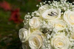 Eheringe auf Brautblumenstrauß Stockbild