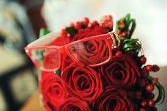 Eheringe auf den Gläsern und einem roten Blumenstrauß Stockbild